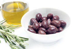 Aceitunas negras de Kalamata en un cuenco y un aceite de oliva blancos, romero GA Imagen de archivo libre de regalías