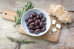 Aceitunas negras de Kalamata, pan, queso feta e hierbas en el wo rústico Fotos de archivo