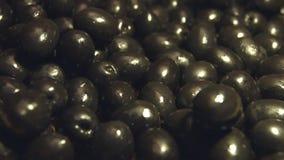 Aceitunas negras en un fondo de madera marrón 2 tiros almacen de metraje de vídeo