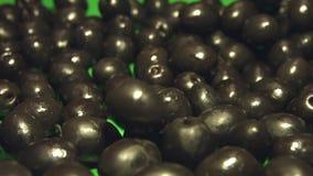 Aceitunas negras en un fondo verde 2 tiros almacen de video