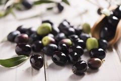 Aceitunas negras en una tabla blanca Fotografía de archivo