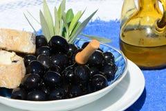 Aceitunas negras, pan y aceite Fotos de archivo libres de regalías