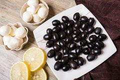 Aceitunas negras, queso de la mozzarella y rebanadas del limón en un fondo marrón Fotografía de archivo