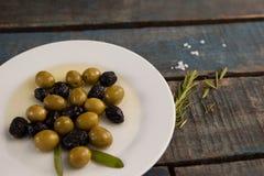 Aceitunas negras verdes y secas con aceite en placa en la tabla Imagen de archivo libre de regalías