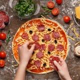 Aceitunas negras y salami de Decorating Pizza With del cocinero fotografía de archivo