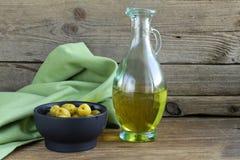 Aceitunas verdes adobadas y una botella de aceite Imagenes de archivo