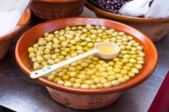 Aceitunas verdes conservadas en vinagre para la venta en una ebullición con una cuchara en el mercado de Sineu, Majorca Imagenes de archivo