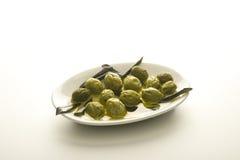 Aceitunas verdes en aceite de oliva con la ramificación en una placa imagen de archivo
