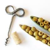 Aceitunas verdes en tazones de fuente, corcho y sacacorchos en blanco Fotografía de archivo libre de regalías