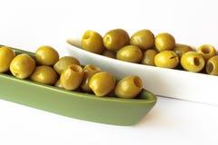 Aceitunas verdes en tazones de fuente de cerámica en el fondo blanco Foto de archivo libre de regalías