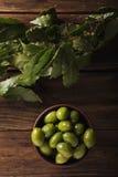 Aceitunas verdes en un cuenco de cerámica en un fondo de madera foto de archivo libre de regalías