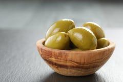 Aceitunas verdes gigantes conservadas en vinagre en cuenco verde oliva en pizarra Imagenes de archivo