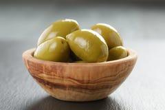Aceitunas verdes gigantes conservadas en vinagre en cuenco verde oliva en pizarra Imagen de archivo libre de regalías