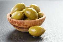 Aceitunas verdes gigantes conservadas en vinagre en cuenco verde oliva en pizarra Foto de archivo