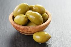 Aceitunas verdes gigantes conservadas en vinagre en cuenco verde oliva en pizarra Fotografía de archivo libre de regalías