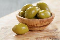 Aceitunas verdes gigantes en cuenco verde oliva en la madera Imagen de archivo libre de regalías
