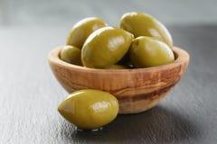 Aceitunas verdes gigantes en cuenco verde oliva en pizarra Imagenes de archivo