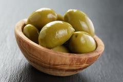 Aceitunas verdes gigantes en cuenco verde oliva en pizarra Fotos de archivo libres de regalías