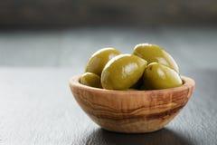 Aceitunas verdes gigantes en cuenco verde oliva en pizarra Fotografía de archivo libre de regalías