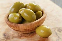 Aceitunas verdes gigantes saladas en cuenco verde oliva en de madera Imagenes de archivo