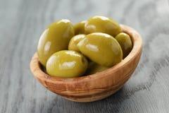 Aceitunas verdes gigantes saladas en cuenco verde oliva en de madera Fotografía de archivo