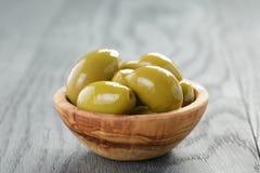 Aceitunas verdes gigantes saladas en cuenco verde oliva en de madera Foto de archivo libre de regalías