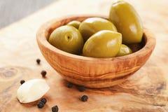 Aceitunas verdes gigantes saladas en cuenco verde oliva en la tabla de madera Fotografía de archivo