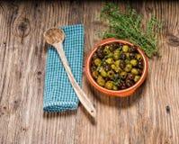 Aceitunas verdes y negras con la cuchara de madera Imagen de archivo
