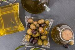 Aceitunas verdes y negras con las botellas del aceite de oliva Foto de archivo