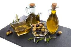 Aceitunas verdes y negras con las botellas del aceite de oliva Fotos de archivo libres de regalías