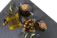 Aceitunas verdes y negras con las botellas del aceite de oliva Foto de archivo libre de regalías