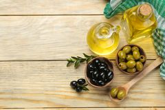 Aceitunas verdes y negras en un cuenco de madera con las hojas y el aceite de oliva en una tabla de madera natural Visi?n superio fotos de archivo libres de regalías