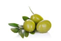 Aceitunas verdes y rama de olivo conservadas en vinagre en un blanco Foto de archivo libre de regalías