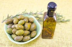 Aceitunas verdes y una botella de aceite de oliva virginal Fotografía de archivo
