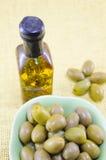 Aceitunas verdes y una botella de aceite de oliva virginal Fotos de archivo libres de regalías