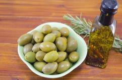 Aceitunas verdes y una botella de aceite de oliva virginal Foto de archivo