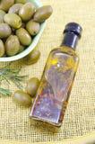 Aceitunas verdes y una botella de aceite de oliva virginal Foto de archivo libre de regalías