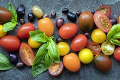 Aceitunas y albahaca de los tomates del fondo de la comida Foto de archivo