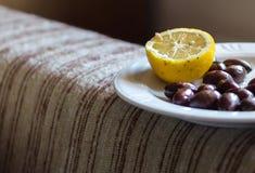 Aceitunas y limón en una placa Imagenes de archivo