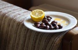 Aceitunas y limón en una placa Imágenes de archivo libres de regalías
