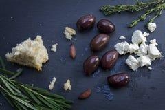 Aceitunas y queso feta de Kalamata con pan e hierbas en una oscuridad Foto de archivo