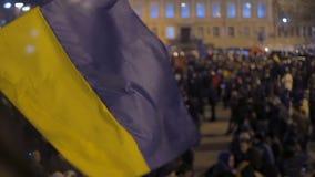 Acenando a bandeira azul e amarela com fundo unfocused da multidão, símbolo nacional filme