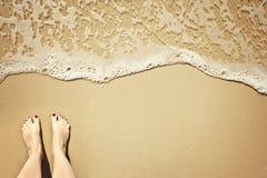 Acene na praia, pés à esquerda Imagens de Stock