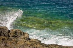 Acene a quebra na rocha com o oceano do verde azul foto de stock