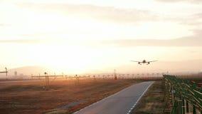 Acepille en la puesta del sol, tierras del aeroplano en el aeropuerto, avión vuela bajo la preparación para aterrizar en el aerop metrajes