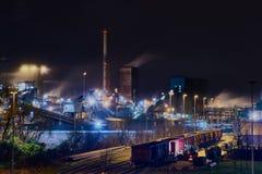 Acería en Duisburgo, Alemania, en la noche con un tren en el frente de la escena - muy surrealista Foto de archivo libre de regalías