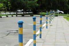 acera cerca de la casa y del inmóvil amarillo azul del polo del estacionamiento consolidados contra la entrada de vehículos Relev Imágenes de archivo libres de regalías