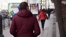 Acera con la gente que camina en la calle con los edificios, camino con los coches m?viles almacen de video