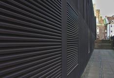 Acera y pared negra con los respiraderos grandes del aire acondicionado que forman las líneas convergentes que llevan hacia pasos fotografía de archivo