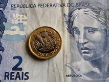acercamiento al billete de banco brasileño de dos reais y a la moneda de una libra esterlina